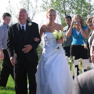 A father walks his daughter down the aisle