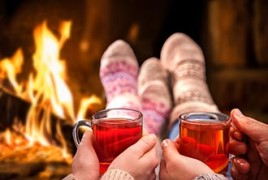 Couple drinking cider by a fire