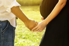 Man and pregnant woman holding hands
