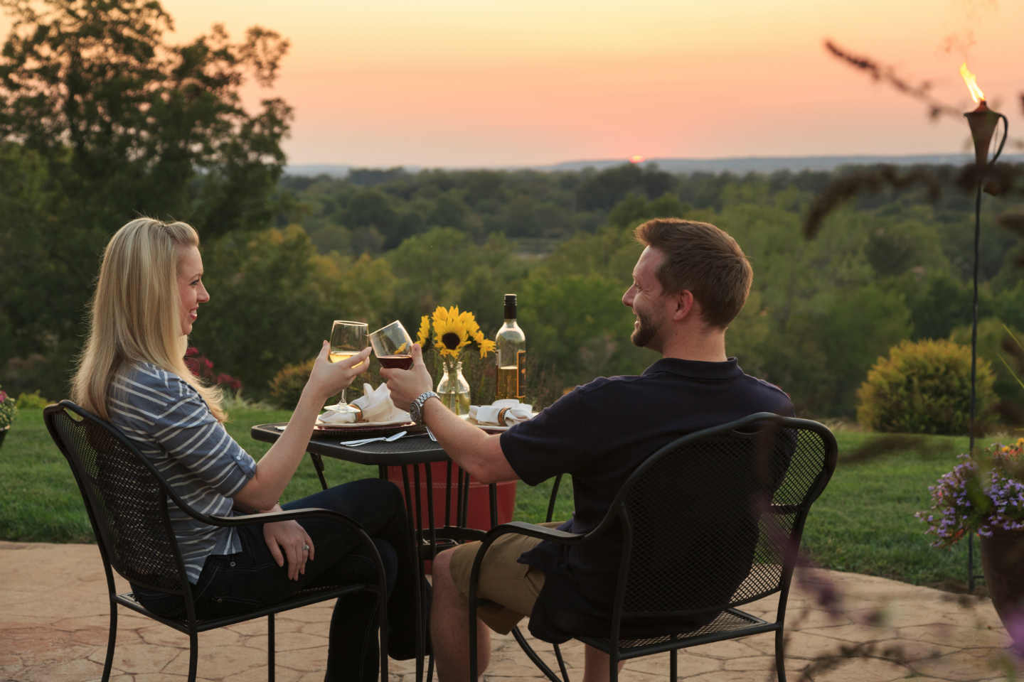 Couple drinking wine on the patio at sunset