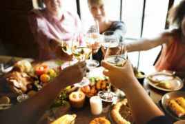 People toasting with glasses of white wine over dinner
