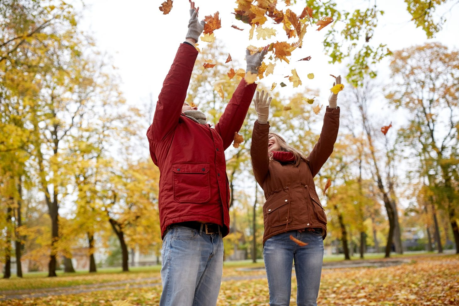 Happy couple throwing the autumn leaves in the air