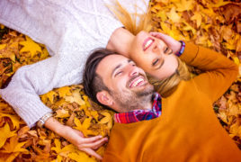Smiling couple laying in a pile of fall leaves