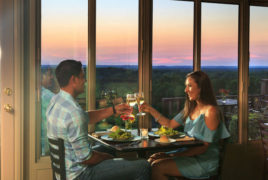 a couple dining with the sunset in the background